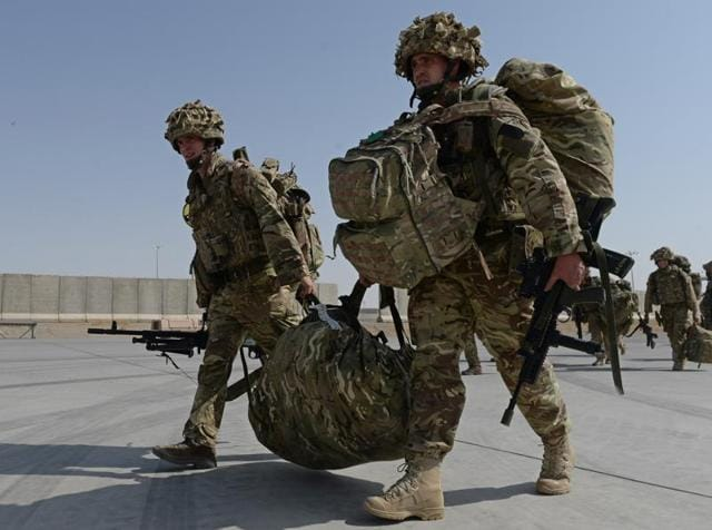 A file picture shows British soldiers walking with their gear after arriving in Kandahar.