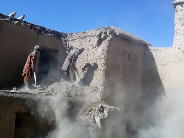 Afghan men clear rubble of an earthquake-damaged house in Kishim District of Badakhshan Poravince.