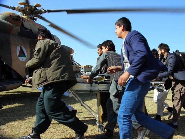 Afghan relatives and medical personnel use a stretcher to transport an injured child towards a waiting Afghan military helicopter at Takhar Province.