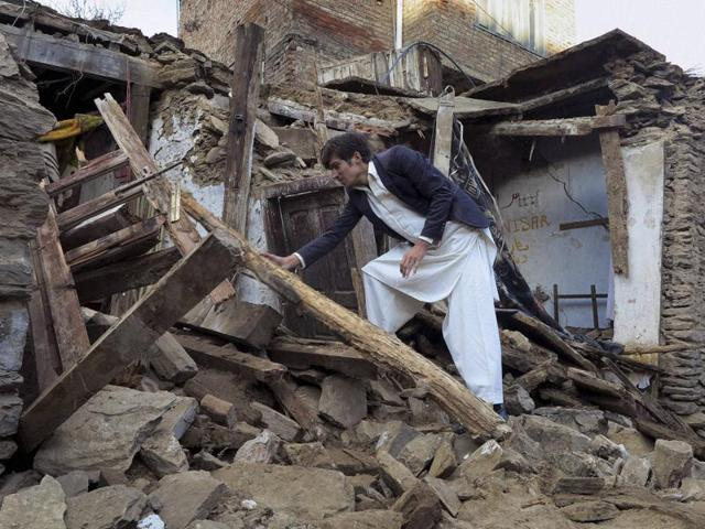 A Pakistani boy examines a house damaged caused by massive earthquake in Mingora, the main town of Swat valley.