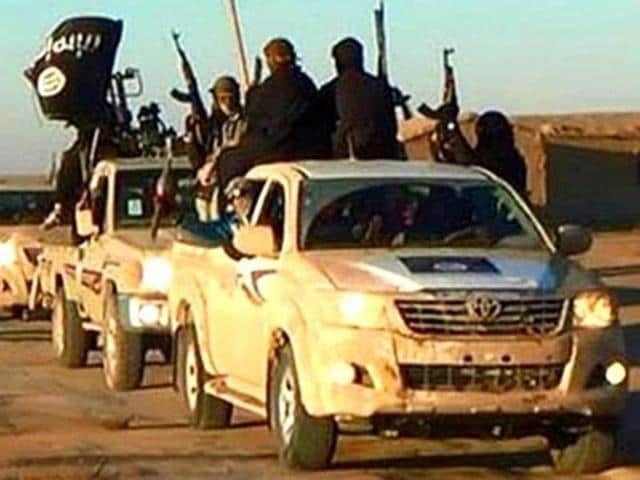 In this undated photo released by a militant website, militants of the Islamic State group hold up their weapons and wave its flags on their vehicles in a convoy on a road leading to Iraq, while riding in Raqqa city in Syria.