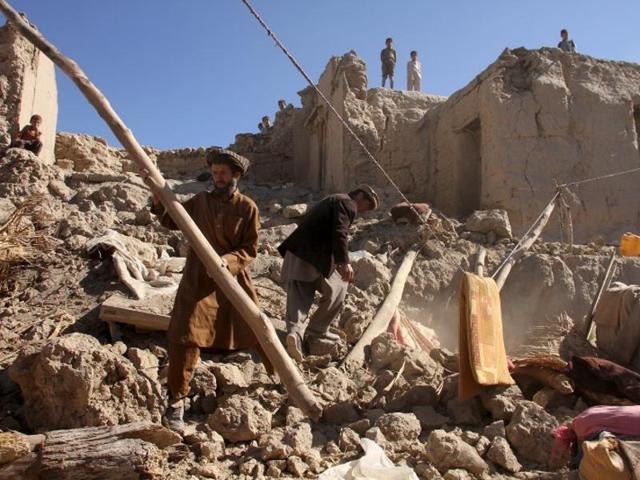 Men look for their belongings after an earthquake in Kishim district of Badakhshan province, Afghanistan.