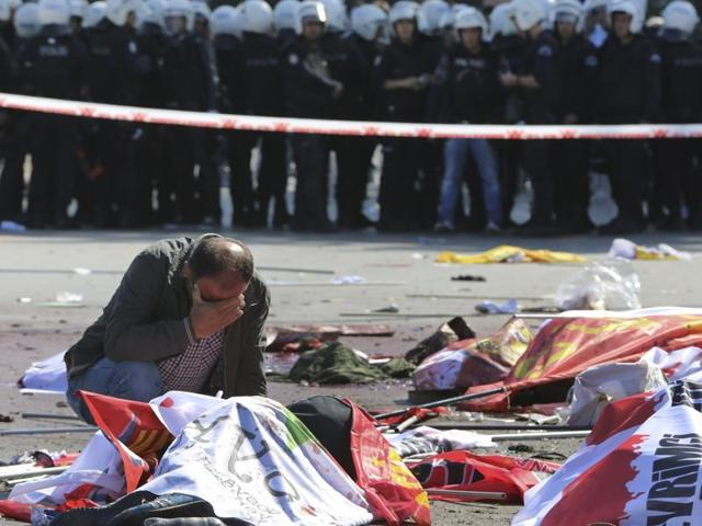 A man cries over the body of a victim, at the site of an explosion in Ankara, Turkey. The two bomb explosions targeting a peace rally in the capital Ankara killed dozens of people and injured scores of others.