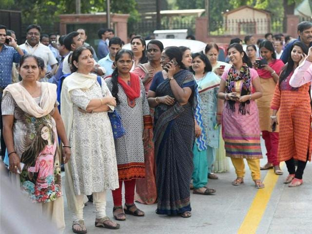 Employees come out of their offices after an earthquake in New Delhi on Monday.