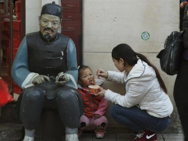 A woman feeds a child in Beijing, China.