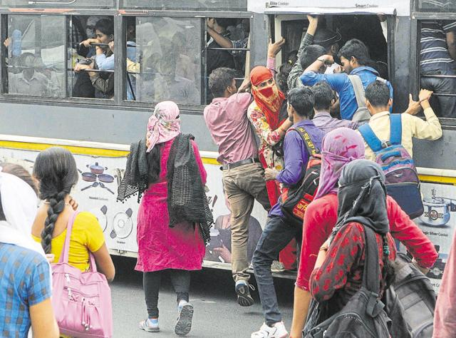 Students and other commuters compete to board a moving low-floor bus due to the strike by mini bus operators, on Tonk Road in Jaipur on Wednesday.