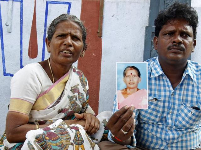 Malliga, sister, and Mohan, son of Kasthuri Munirathinam, display his mother's photograph in Chennai.