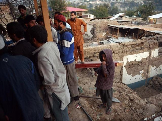 Afghan Red Crescent Society (ARCS) workers distribute aid in the form of household goods to earthquake affected people in Behsud district of Nangarhar Province.