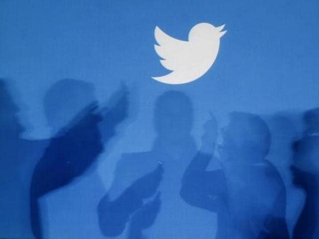The shadows of people holding mobile phones are cast onto a backdrop projected with the Twitter logo in this illustration picture taken in Warsaw .