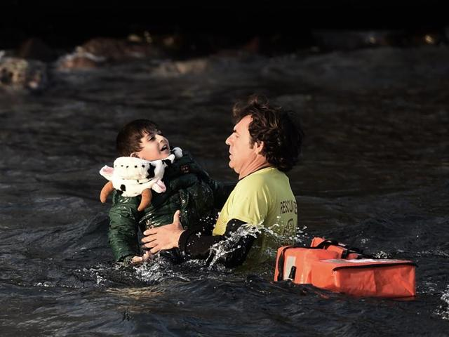 A Spanish lifeguard saves a migrant child as the boat he had boarded with other migrants and refugees sinks off the Greek island of Lesbos after crossing the Aegean sea from Turkey on October 30, 2015.