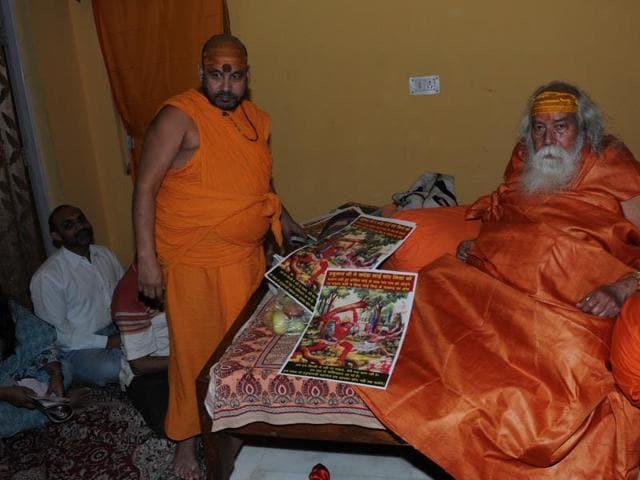 Shankaracharya Swami Swaroopanand Saraswati showing posters prepared by his disciples.