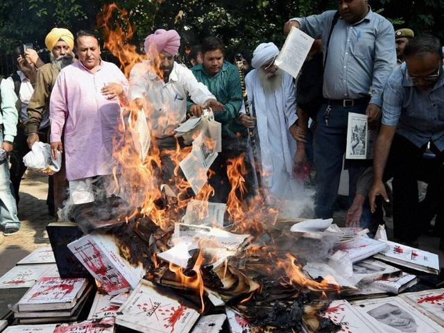 Sikh protesters on Friday burnt books questioning the authors' silence on 1984 anti-Sikh riots issue in New Delhi.