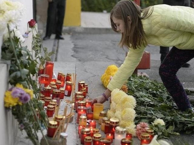 A woman lights a candle outside a nightclub, where a fire broke out on Friday, in Bucharest, Romania.