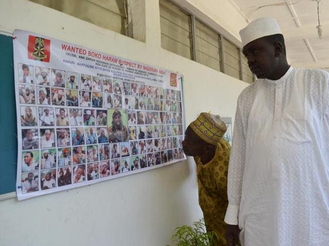 In this photo taken Friday, Oct. 30, 2015, a poster featuring wanted Boko Haram members, pasted onto the wall by Nigeria army in Maiduguri, Nigeria.