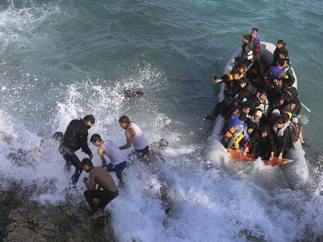 Refugees and migrants abort their effort on a dingy as they set out, trying to travel from the Turkish coast to the Greek island of Chios.