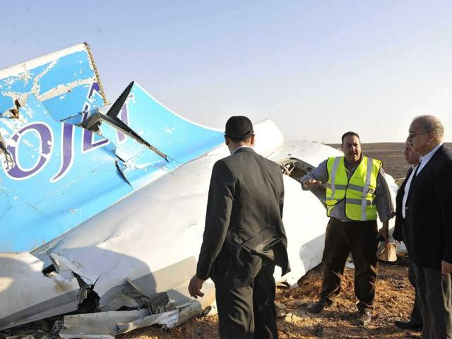 In this photo released by the Egypt Prime Minister's Office, Sherif Ismail, right, looks at the remains of a crashed passenger jet in Hassana. (Suliman el-Oteify/Egyptian Prime Minister's Office via AP)