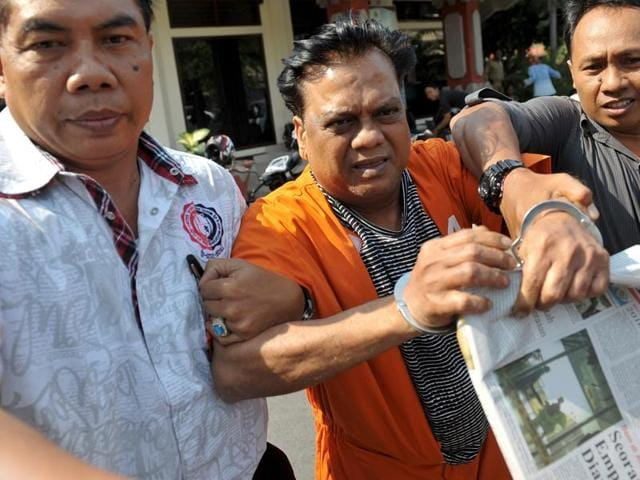 Indonesian plainclothes policemen escort Indian gangster Rajendra Nikalje (C), widely known as Chhota Rajan, as they walk at Denpasar police office.