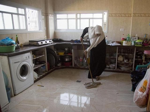 Um Alabed al-Zaza mops her new kitchen in a house that was completely destroyed during the last summer's war between Israel and Hamas, in Gaza City.