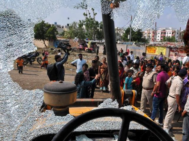 Protesting women of Ramabai Nagar stand in front of a bulldozer.