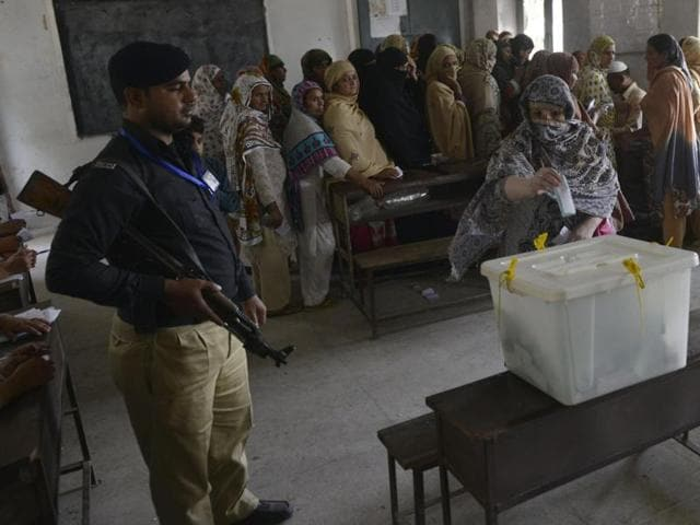 A Pakistan policeman watches as a voter casts a ballot during a local government election at a polling station in Lahore on October 31, 2015.