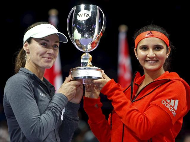 Sania Mirza and Martina Hingis celebrate after winning the women's doubles final of the WTA Finals in Singapore on November 1, 2015.