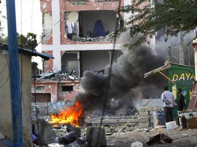 Somali policemen carry a wounded person to an ambulance outside the Sahafi Hotel in Mogadishu, Somalia.