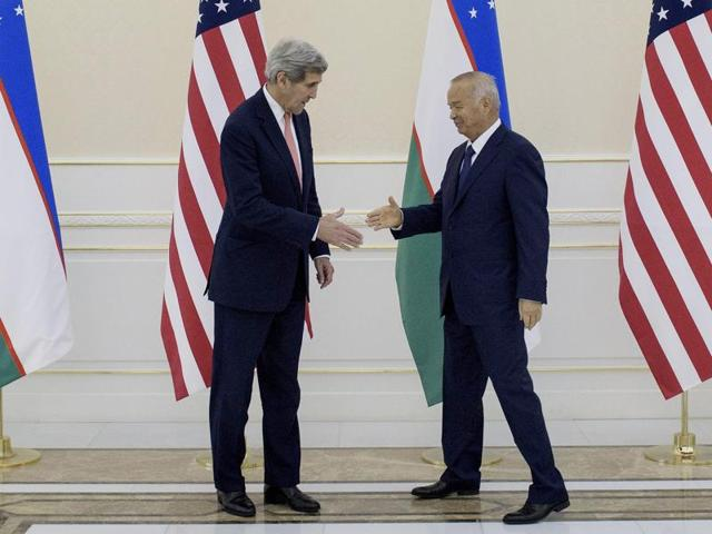 Uzbek President Islam Karimov (R) shakes hands with US secretary of state John Kerry before a meeting at the Palace of Forums on the President's Residential Compound in Samarkand.