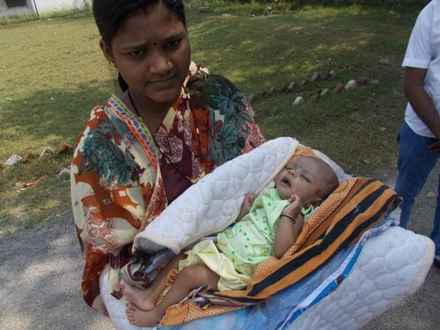 Surrendered Maoist Tijo cuddles her baby in her arms, in Chhattisgarh.