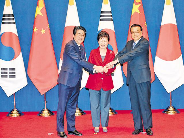 South Korean President Park Geun-hye (C) shakes hands with Chinese Premier Li Keqiang (R) and Japanese Prime Minister Shinzo Abe at the Presidential Blue House in Seoul on Sunday.