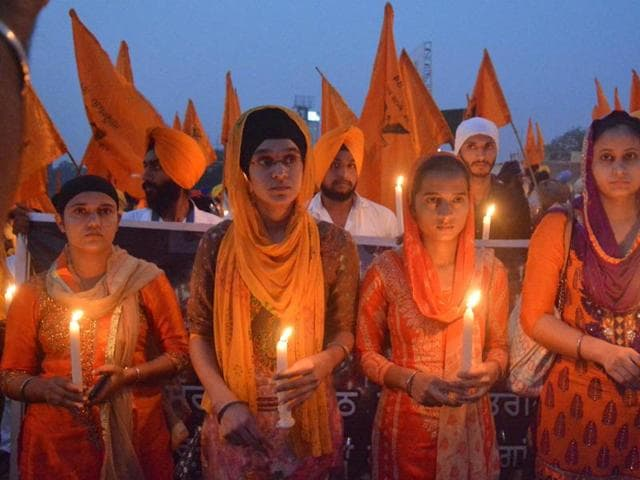 Dal Khalsa activists seeking justice for the 1984 riot victims during a candlelight vigil in Amritsar on Monday.