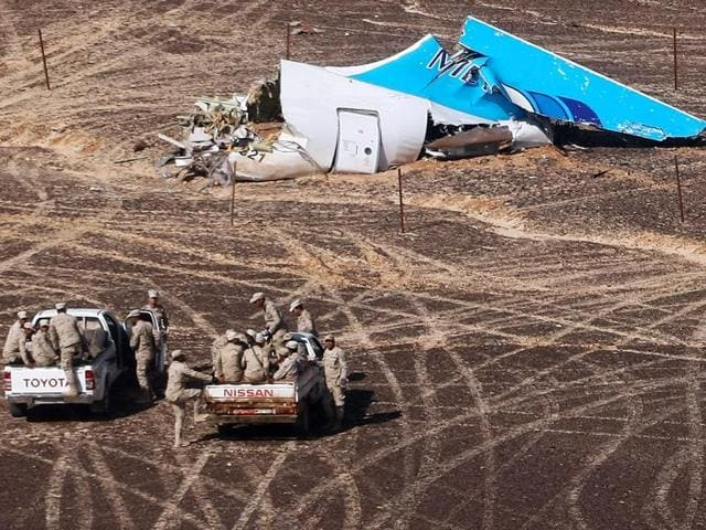 In this photo provided by Russian Emergency Situations Ministry, Egyptian military approach a plane's tail at the wreckage of a passenger jet bound for St Petersburg in Russia that crashed in Hassana, Egypt.