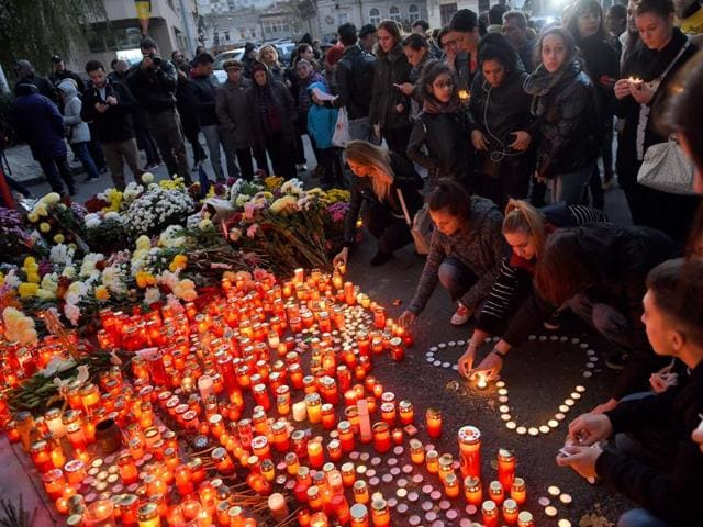 People light candles to commemorate the victims outside the nightclub Colectiv in Bucharest on October 31, 2015, a day after a mortal fire.