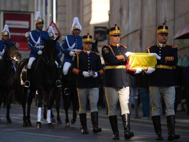 Romanian guard soldiers carry the gilded silver casket containing the heart of the Queen Marie of Romania covered by a national flag on their way to the Pelisor Palace in Bucharest.