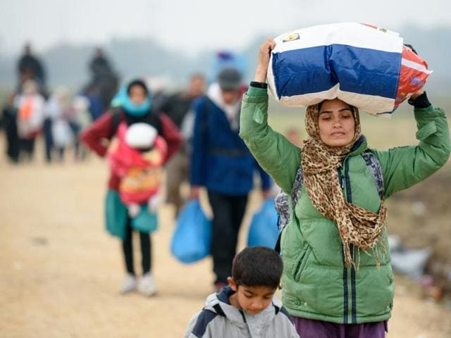 A woman carries her belongings as migrants and refugees walk towards buses to be taken to a refugee centers after crossing Croatian-Slovenian border in Rigonce. More than 700,000 refugees and migrants have reached Europe's Mediterranean shores so far this year, amid the continent's worst migration crisis since World War II, according to the UN refugee agency.