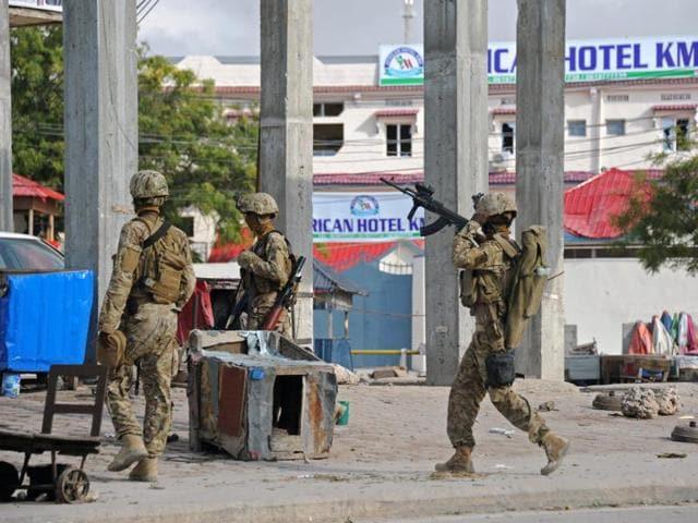 Somali policemen carry a wounded person to an ambulance outside the Sahafi Hotel in Mogadishu, Somalia Sunday, Nov. 1, 2015.