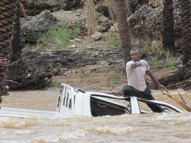 A man gestures as he tries to save a vehicle swept away by flood waters in Yemen's island of Socotra. A rare tropical cyclone packing hurricane-force winds killed three people and injured scores on the island.