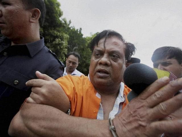 Indian fugitive Chhota Rajan  is escorted by plain-clothed police officers for questioning in Bali, Indonesia, Tuesday, Nov. 3, 2015.  Rajan may be brought to India on Wednesday.