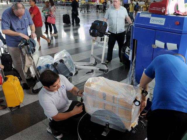 Passengers get their luggage wrapped in plastic protection wrap in Manila airport on November 4, 2015.