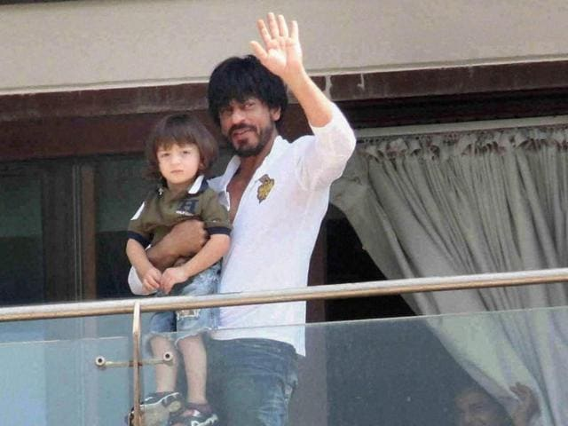 Actor Shah Rukh Khan with son Abram waves to fans and well-wishers gathered outside his residence.