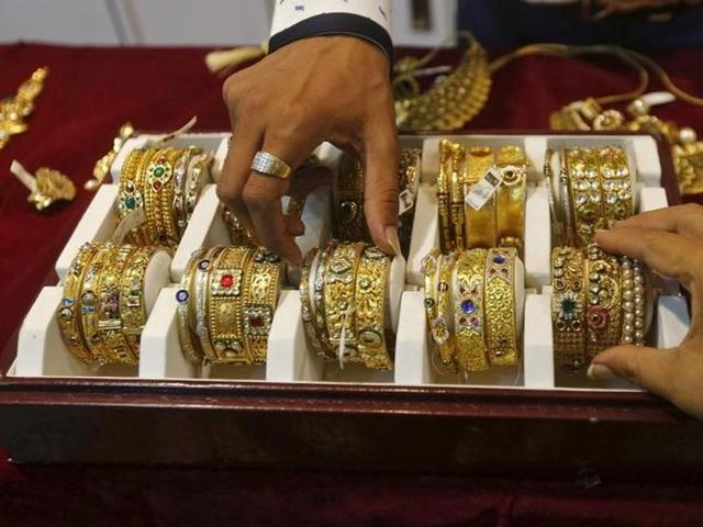 A saleswoman places a gold necklace on a shelf at a showroom in Mumbai.