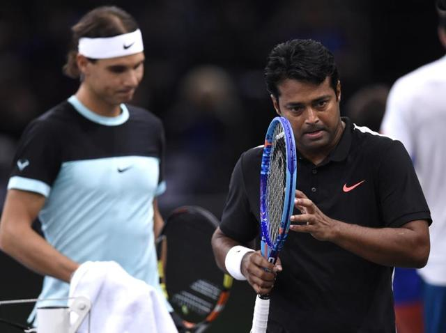 Spain's Rafael Nadal (R) serves the ball past India's Leander Paes (L) during their doubles match against Britain's Dominic Inglot and Sweden's Robert Lindstedt at the ATP World Tour Masters 1000 indoor tennis tournament in Paris.