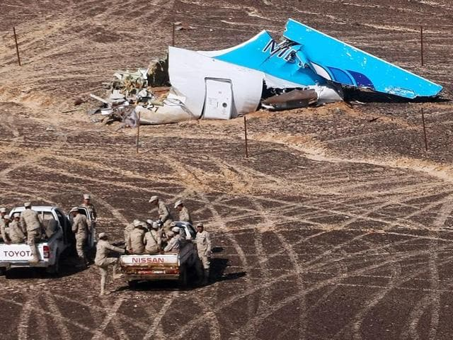 In this photo provided by Russian Emergency Situations ministry, Egyptian military approach the plane's tail at the wreckage of a passenger jet bound for St Petersburg in Russia that crashed in Hassana, Egypt.