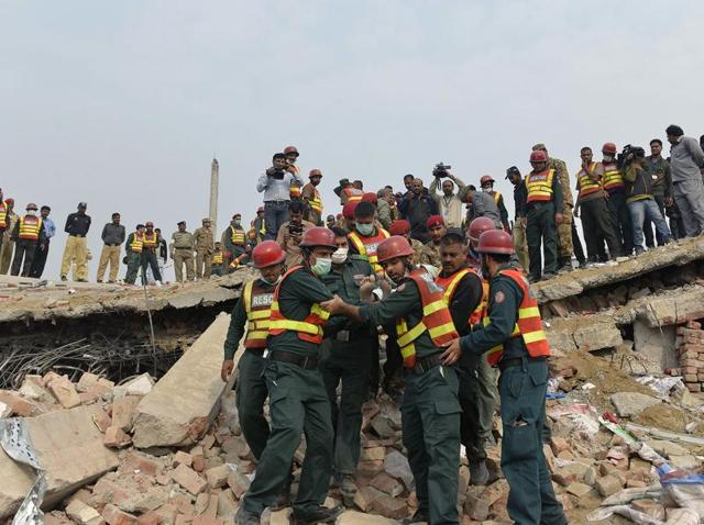 Pakistani rescuers move a man rescued from under the rubble of a collapsed factory on the outskirts of Lahore. Pakistani rescuers have pulled 99 people from the rubble of a collapsed factory and are searching for an unknown number of others believed still trapped in a disaster that has killed at least 23.