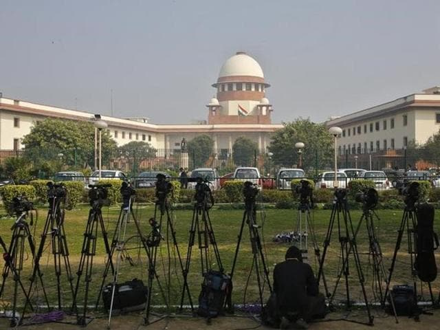 A television journalist sets his camera inside the premises of the Supreme Court in New Delhi.