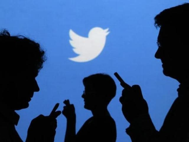 People holding mobile phones are silhouetted against a backdrop projected with the Twitter logo in this illustration picture taken in Warsaw .