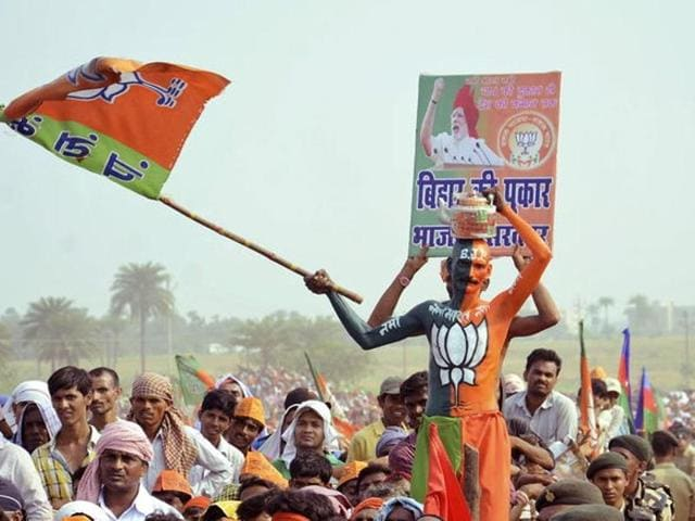 A supporter of Bharatiya Janata Party (BJP) waves the party flag during an election campaign rally addressed by Prime Minister Narendra Modi (not pictured) in Banka.