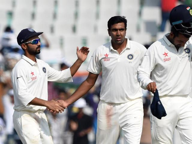 India's Ajinkya Rahane (L) congratulates teammate Ravichandran Ashwin (C) after his dismissal of South Africa's Imran Tahir.
