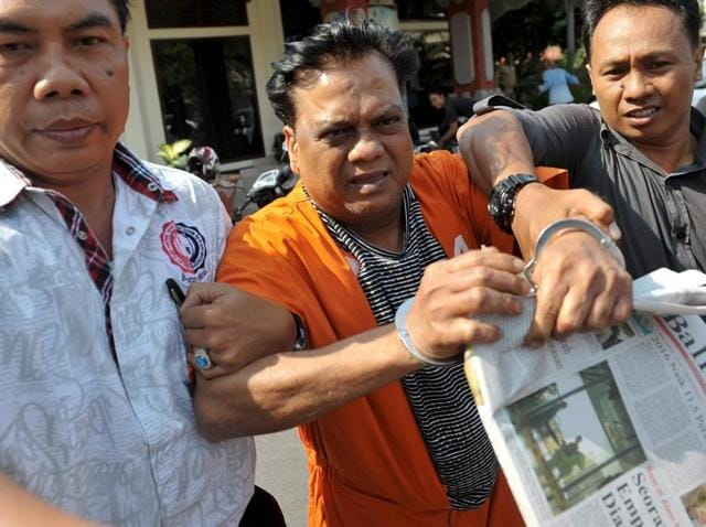 Indonesian plainclothes policemen escort Indian gangster Rajendra Nikalje (C), widely known as Chhota Rajan, as they walk at Denpasar police office October 29, 2015.
