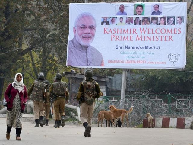A soldier stands guard alongside a poster bearing the image of Prime Minister Narendra Modi near the venue of Modi's scheduled rally in Srinagar on November 6, 2015.