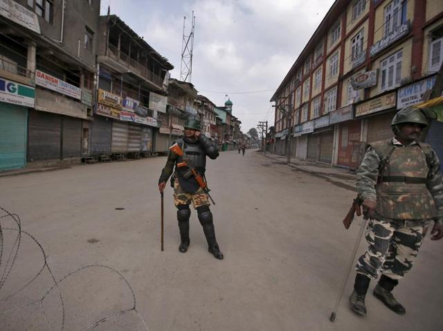 Security personnel stand guard along a deserted street during restrictions in Srinagar. Security forces have detained Kashmiri separatists to prevent them marching in protest during Prime Minister Narendra Modi's visit, police said, raising tensions in the disputed territory.